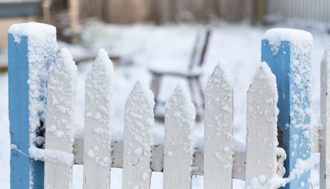 Snow Covered White And Blue Picket Fence With Falling Snow Flake